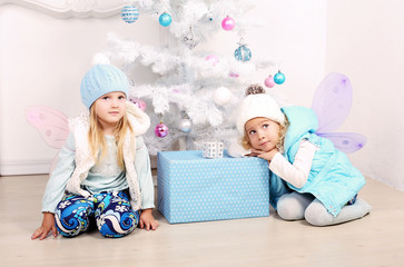 little girls posing beside a decorated Christmas tree
