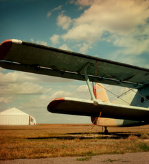 Plane wing against autumn field.
