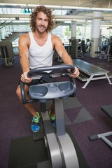 Handsome man working out on exercise bike at gym
