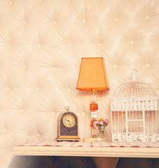 Retro clock, lamp and birdcage backdrop.