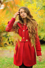 Young fashion woman dressed in red coat in autumn park.
