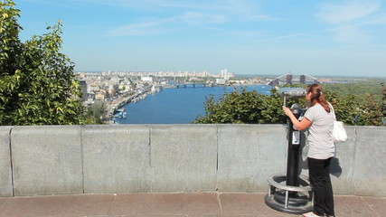 woman watching in huge binocular on viewing platform