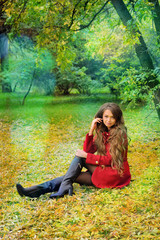 Woman in red sitting in autumn park.