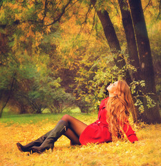 Woman dressed in red coat relaxing in autumn park.