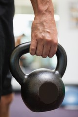 Cropped man holding kettle bell