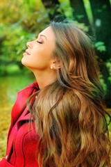 portrait in profile of a young beautiful girl resting in a park.