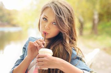 Teenage girl drinking coffee outdoor.