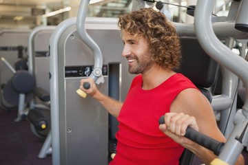 Handsome smiling man working on fitness machine at gym