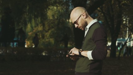 Bald man in sunglasses with phone in the park...