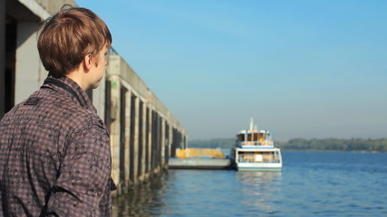 young man watching on river, boat at background in defocus