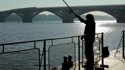 silhouette of fisherman, behind him train rides through bridge