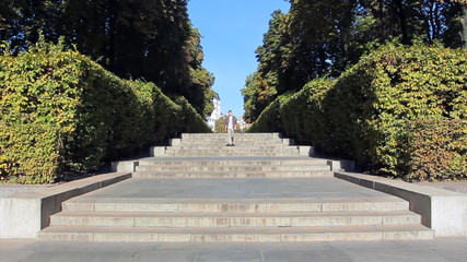 young man walking down stairs in city through well trimmed bush