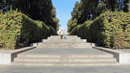 couple walking down stairs in city through well trimmed bush