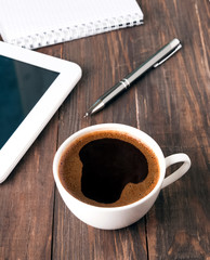 Cup of coffee, tablet and notebook