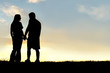 Silhouette of Happy Couple Holding Hands and Talking at Sunset - 72315277