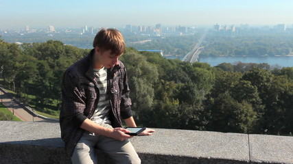 young man reads electronic book, on background view of Kiev