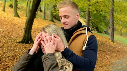 Man surprises woman - young model couple in love - kiss embrace