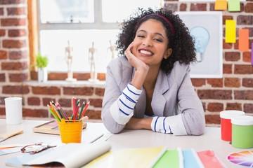 Smiling female interior designer at desk