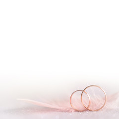 Two Golden Wedding Rings and  Feather -  soft, white