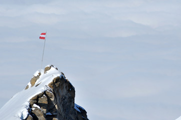 Rocky height in the Alps with the flag of Austria