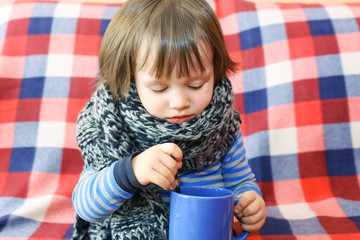 lovely 2 years ill toddler in warm woolen scarf and cup of tea