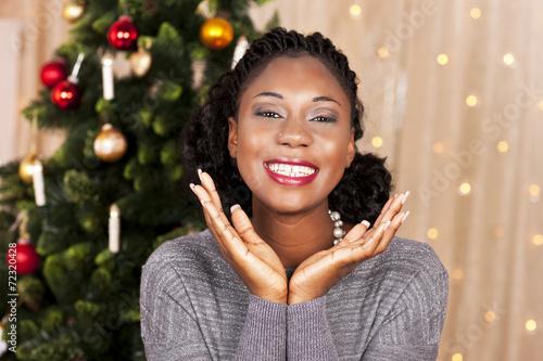 canvas print picture Junge schwarze Frau vor Weihnachtsbaum