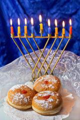 Hanukkah menorah with burning candles and doughnuts
