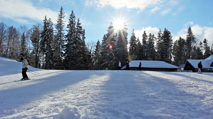 many skiers rides on slopes of mountain peaks before sunset