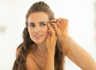 Young woman shaping eyebrows in bathroom