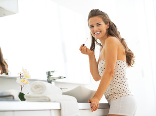 Portrait of happy young woman with lip gloss in bathroom