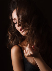 Sexy brunette girl in black lingerie on the black background