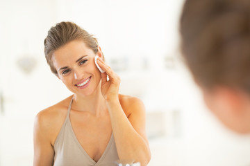 Portrait of happy young woman using cotton pad in bathroom