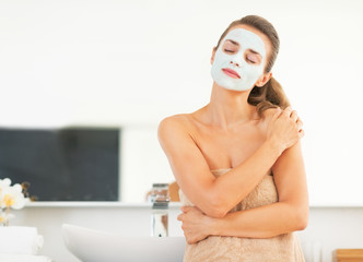 Portrait of young woman with facial cosmetic mask in bathroom