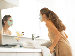 Young woman with facial cosmetic mask looking in mirror