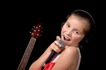 a young girl singing with a microphone