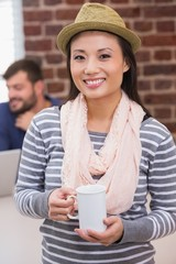 Casual woman with coffee cup in office