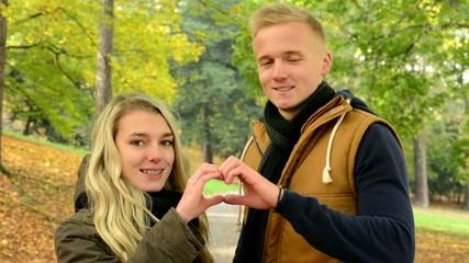 couple forms a heart with their hands - happy couple in love