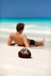 Man lying on a beach on a desert tropical island. Focus on cocon