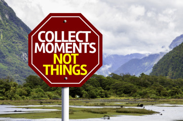 Collect Moments Not Things written on red road sign