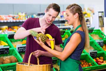 Mann beim Einkaufen im Biomarkt mit Verkäuferin
