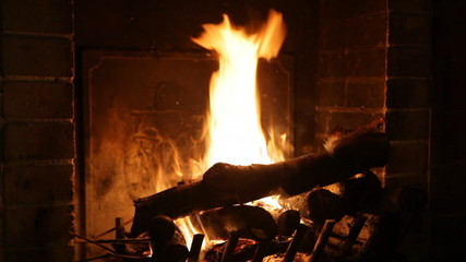 Bright flame of fire burns in an old fireplace
