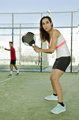 Woman posing showing racket and ready for paddle tennis