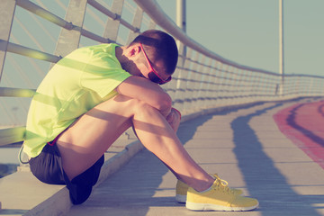 Tired urban jogger making a pause after forcing his body.