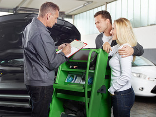 Mechanic with customers in a garage