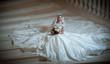Young beautiful luxurious woman in wedding dress sitting