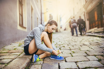 Young female runner tying her shoes