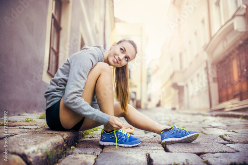 canvas print picture Young female runner tying her shoes