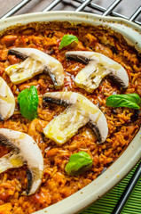 Chicken baked with rice, mushrooms and tomatoes