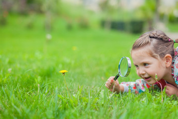 little cute girl with magnifying glass examining flower