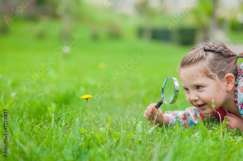 Leinwanddruck Bild little cute girl with magnifying glass examining flower